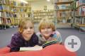 zwei Mädchen lesen gemeinsam in einem Buch