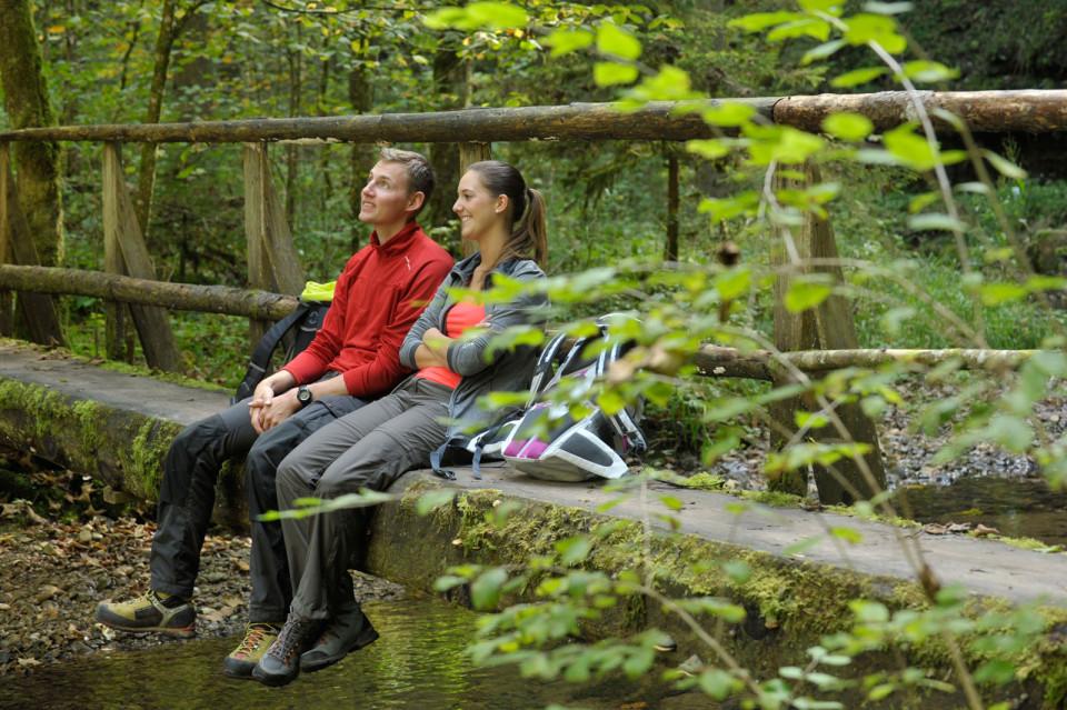 Zwei Personen sitzen auf einem Steg in der Gauchachschlucht