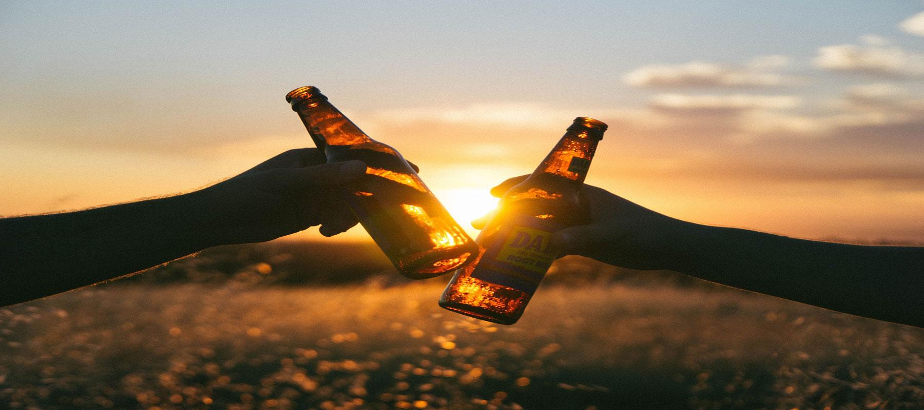 Zwei Menschen stoßen mit zwei Bierflaschen an