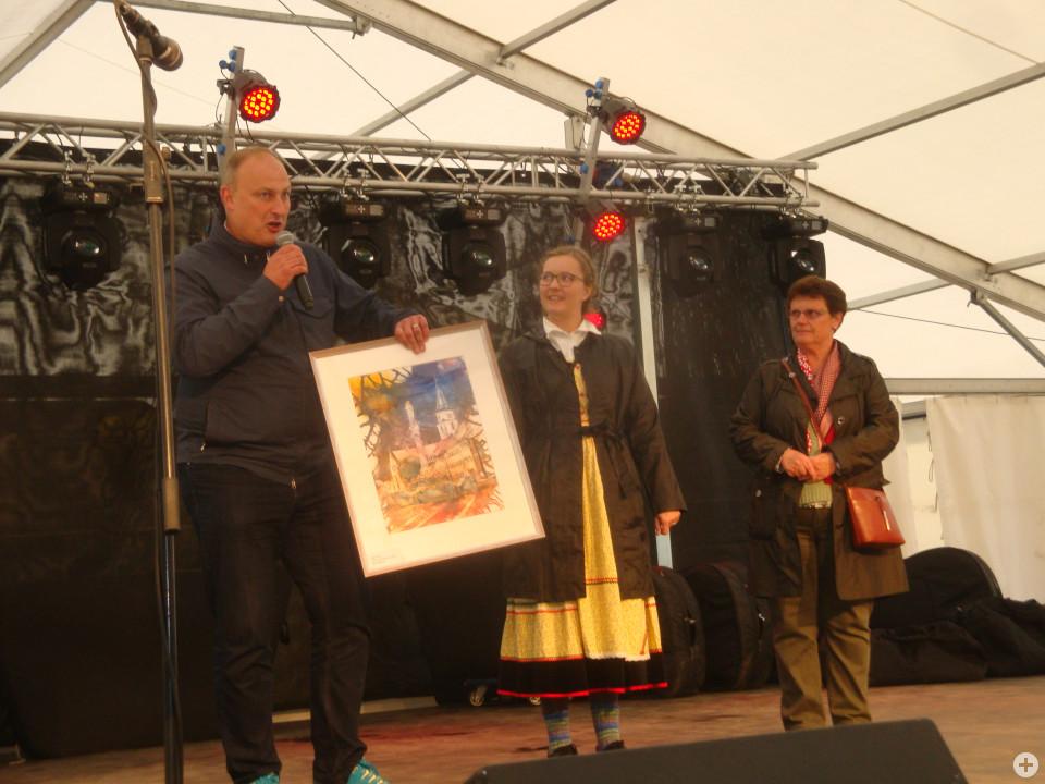 • Bürgermeister Michael Kollmeier überreicht im Festzelt von Mende eine Hüfinger Stadtansicht an Klari Trefak
