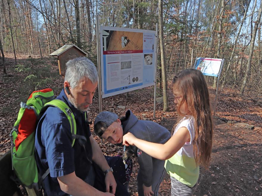 Escape Tour, zwei Kinder und ein Erwachsener testen eine Handwaage