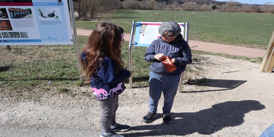 Ein Mädchen und ein Junge versuchen eine kleine Holzschachtel zu öffnen