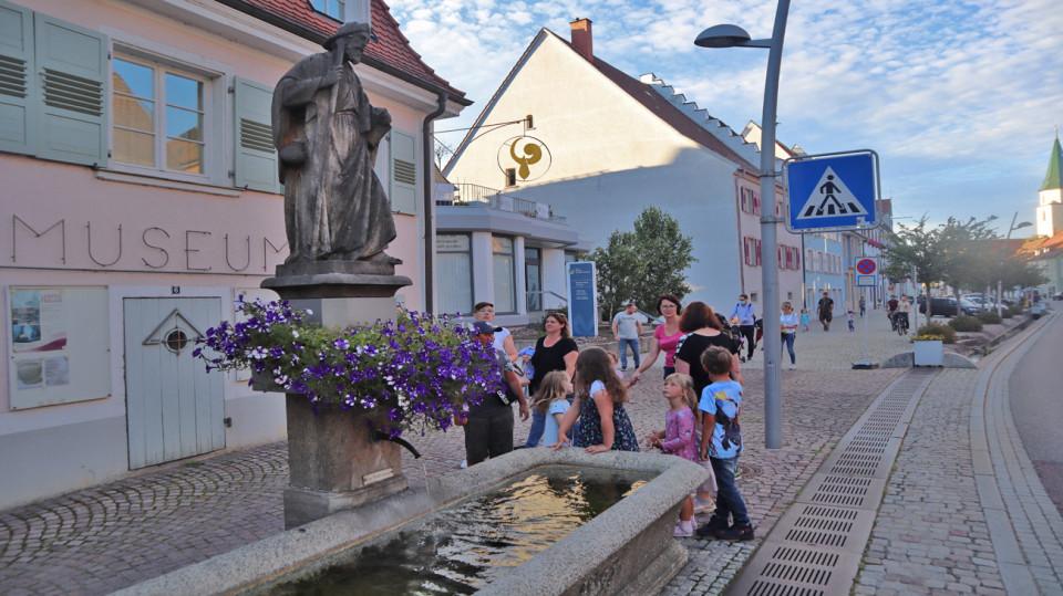 Jakobsbrunnen im Sommer mit Blumen, daneben Kinder und Erwachsene