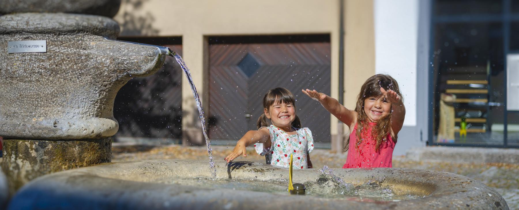 Zwei Mädchen plantschen mit den Händen in einem Brunnen und haben viel Spaß dabei